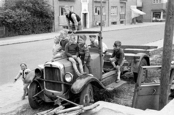 1952. En flok drenge morer sig med en gammel bil.